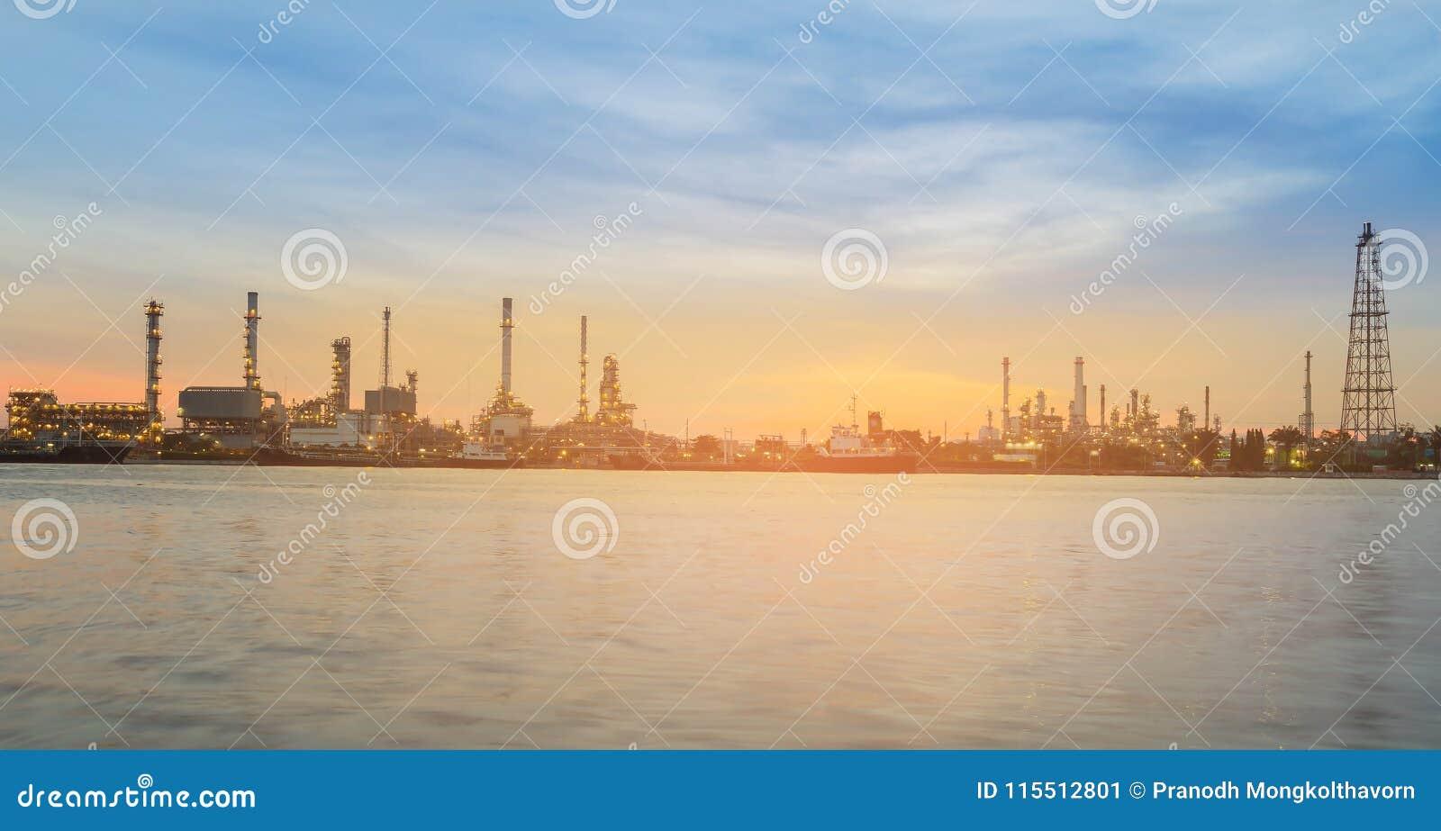 Cielo de la puesta del sol del panorama sobre frente del río de la refinería de petróleo