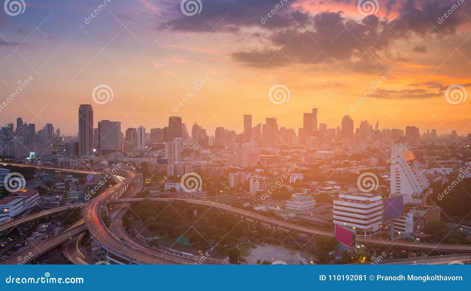 Cielo dramático de la puesta del sol sobre el negocio de la ciudad céntrico