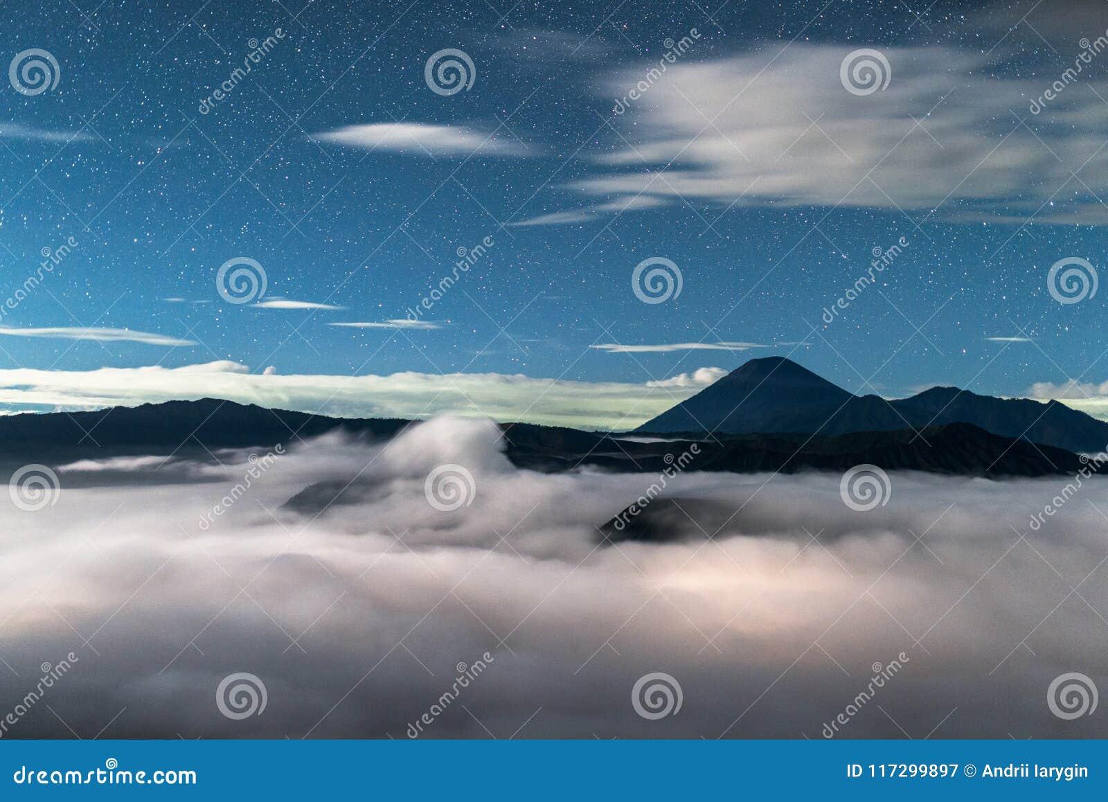 Cielo estrellado en el paisaje con los volcanes en las nubes, Volcan