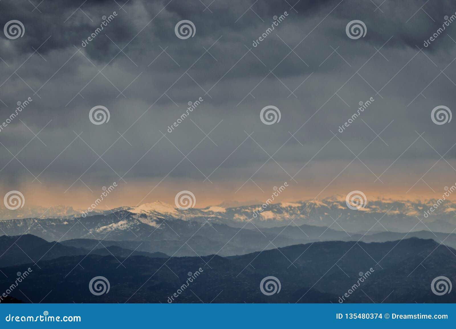 Cielo hermoso con las nubes sobre las montañas nevosas