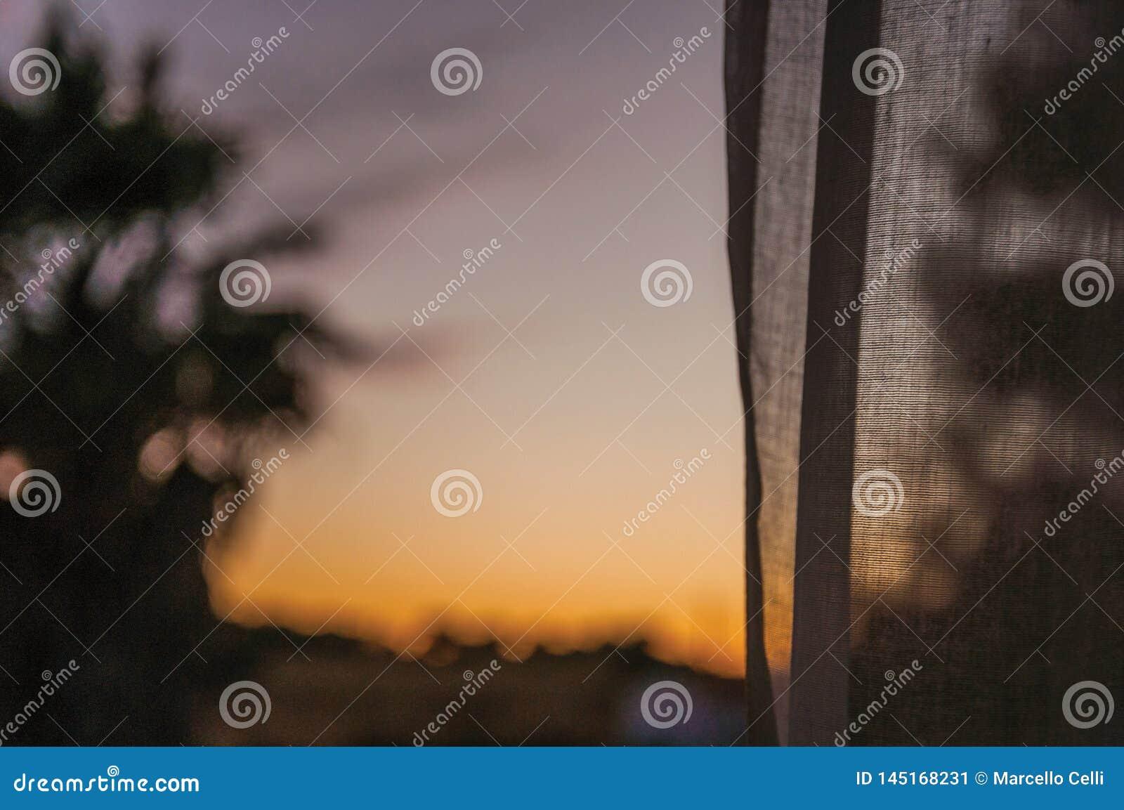 Cielo multicolor en la puesta del sol y una cortina en una granja