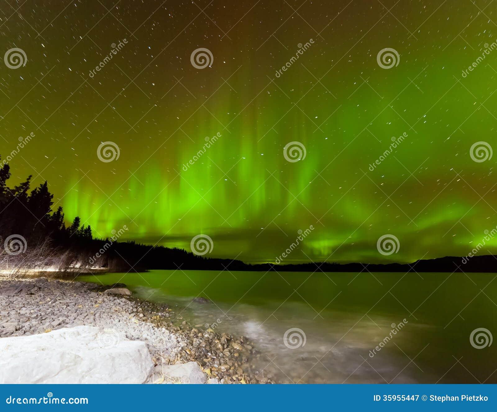 Cielo nocturno del aurora borealis sobre el lago Laberge el Yukón