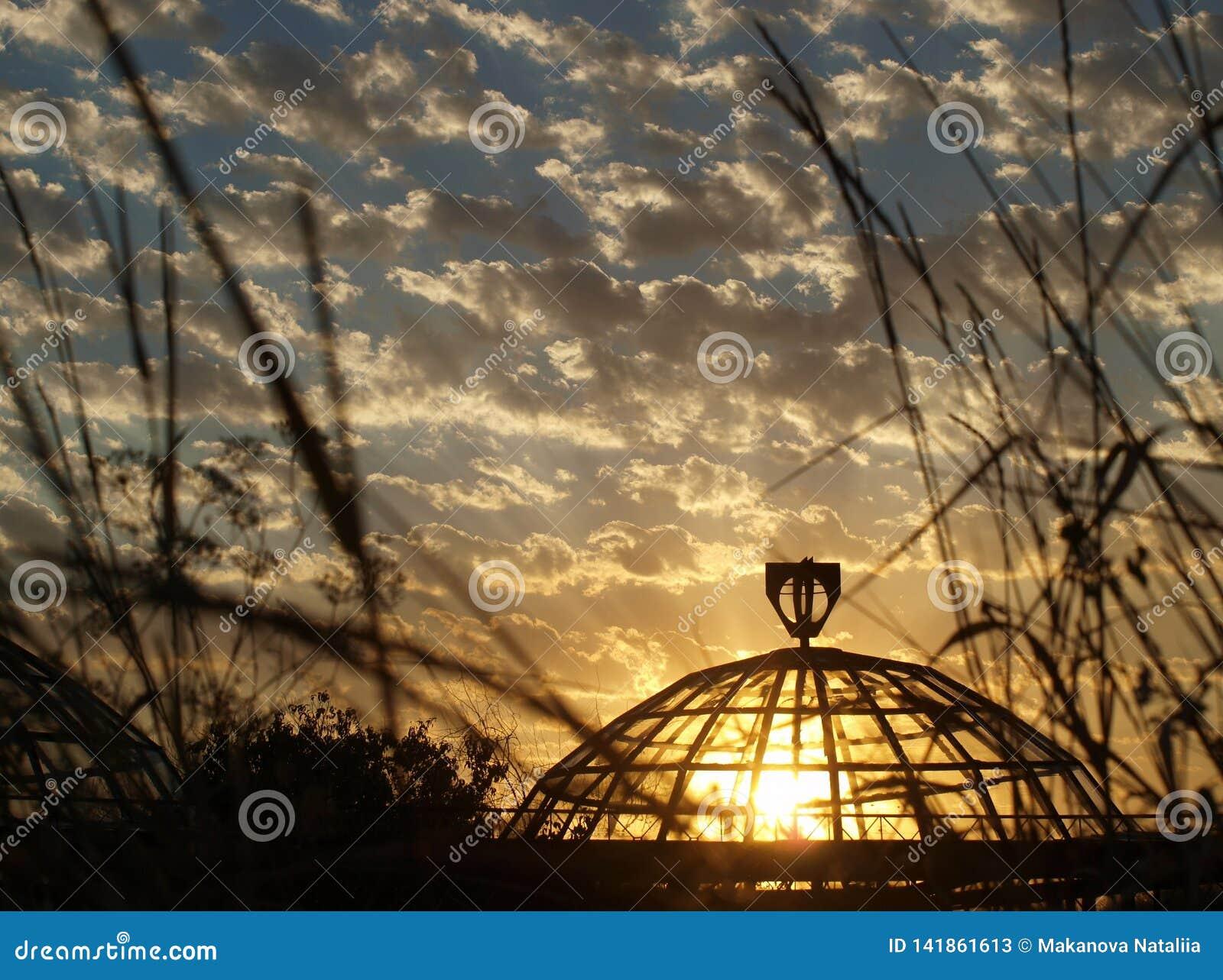 Cielo nublado y sol de la puesta del sol detrás del vidrio de un invernadero viejo