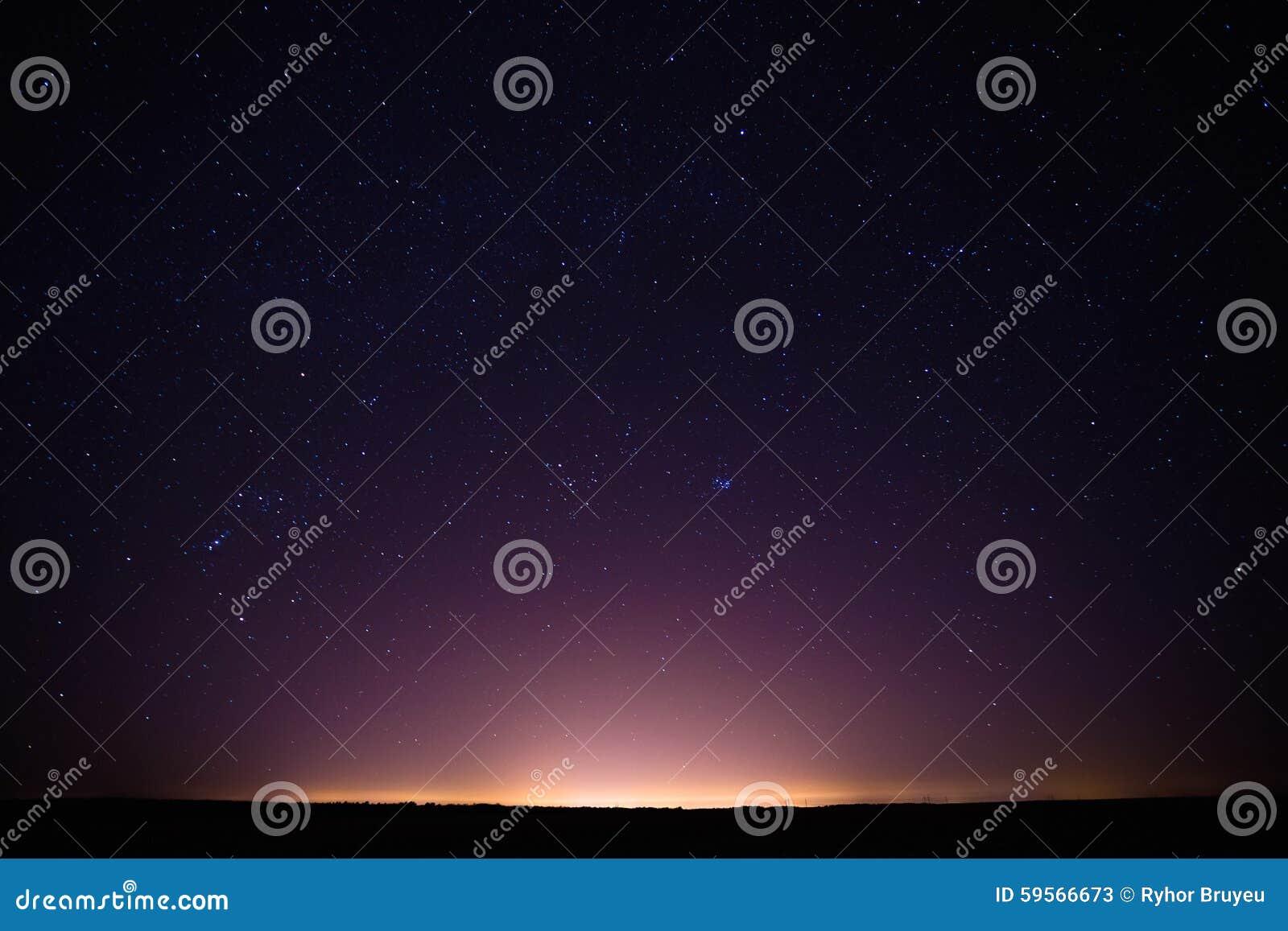 Cielo stellato di notte variopinta sopra la città gialla