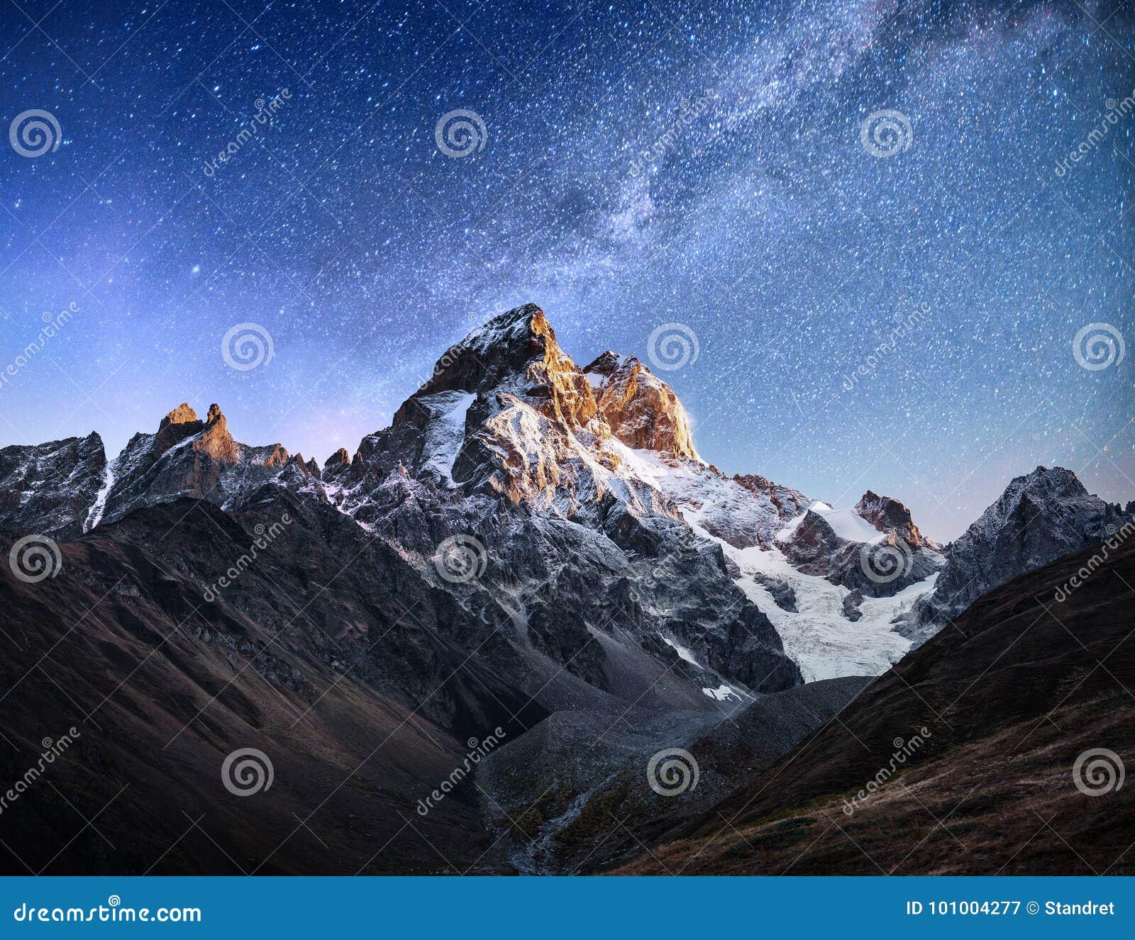 Cielo stellato fantastico Paesaggio di autunno e picchi innevati Cresta caucasica principale Mountain View dal supporto Ushba Mey