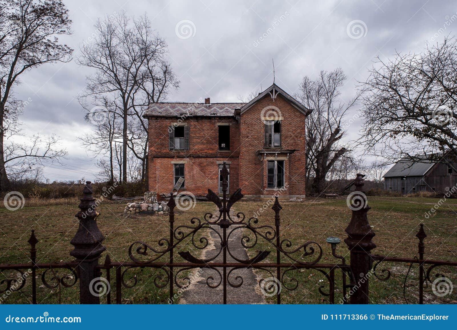Cielos melancólicos y cerca adornada antigua del hierro - casa abandonada - Ohio