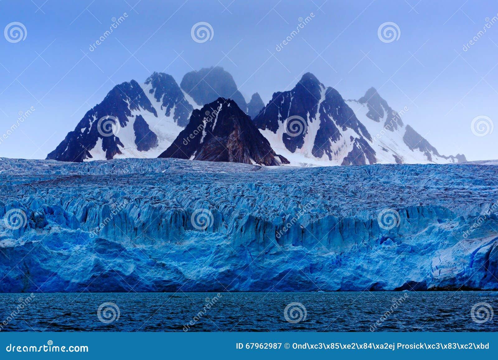 Ciemna zimy góra z śniegiem, błękitny lodowa lód z morzem w przedpolu, Svalbard, Norwegia, Europa