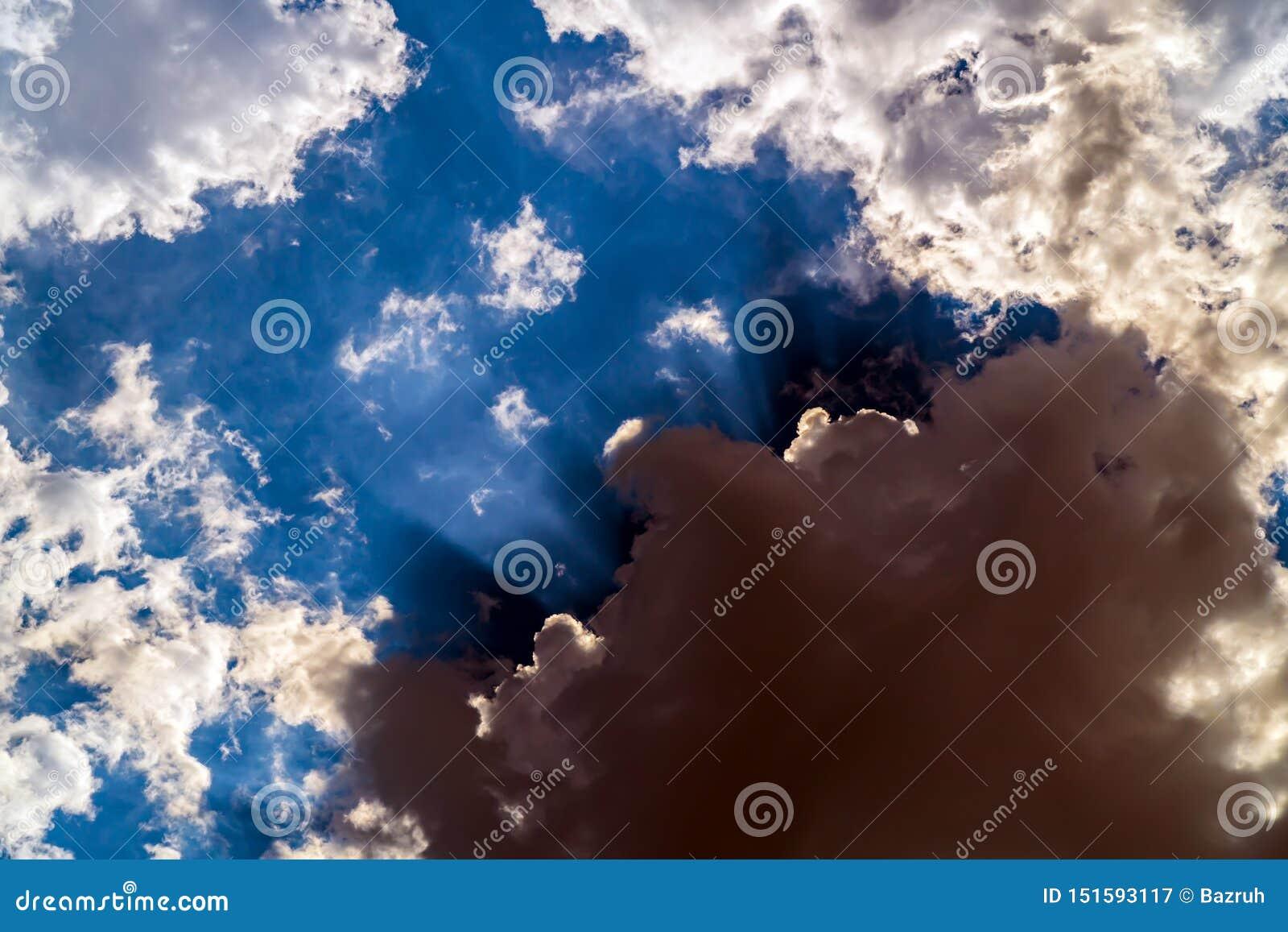 Ciemne burz chmury na jaskrawym niebieskim niebie