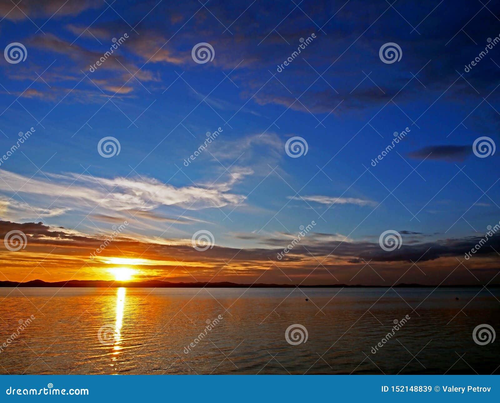Ciemnienie zmierzchu niebo nad jeziorem z kolorowymi chmurami, Złota godzina