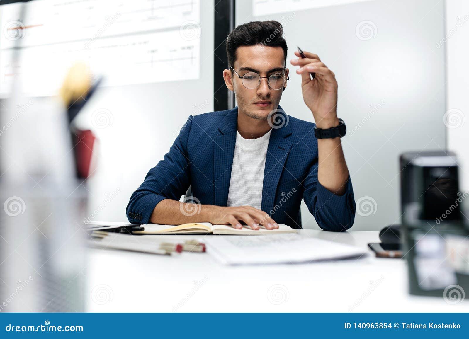 Ciemnowłosy młody architekt w szkłach w niebieskiej marynarce i pracuje z dokumentami na biurku w biurze