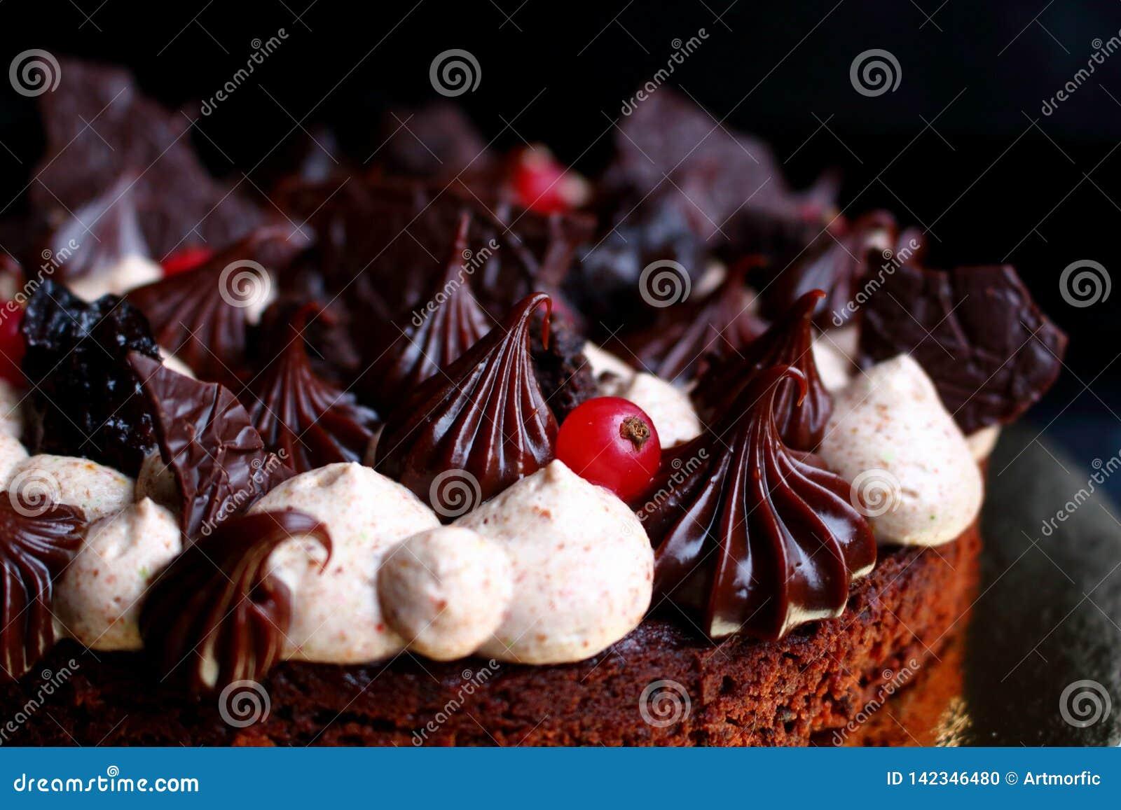 Ciemny czekoladowy tort z śmietanką, ganache i jagodami uderzącymi,