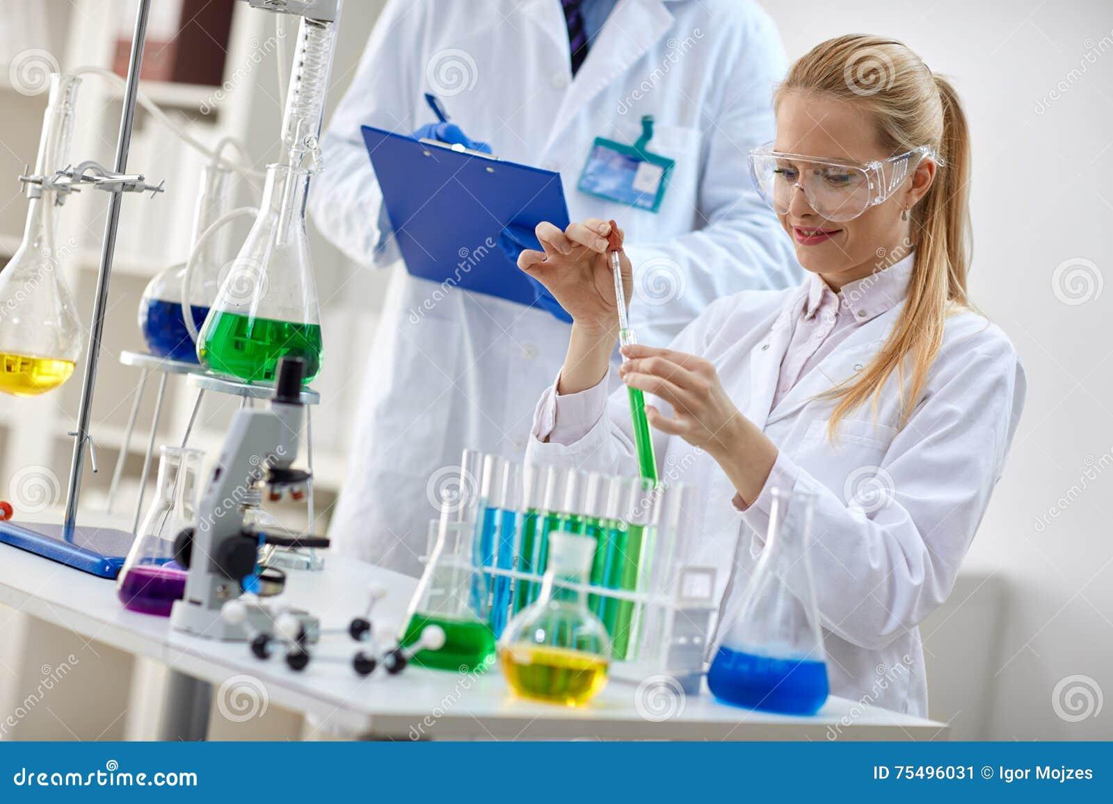 Científico de sexo femenino sonriente que usa el líquido de la química para la investigación