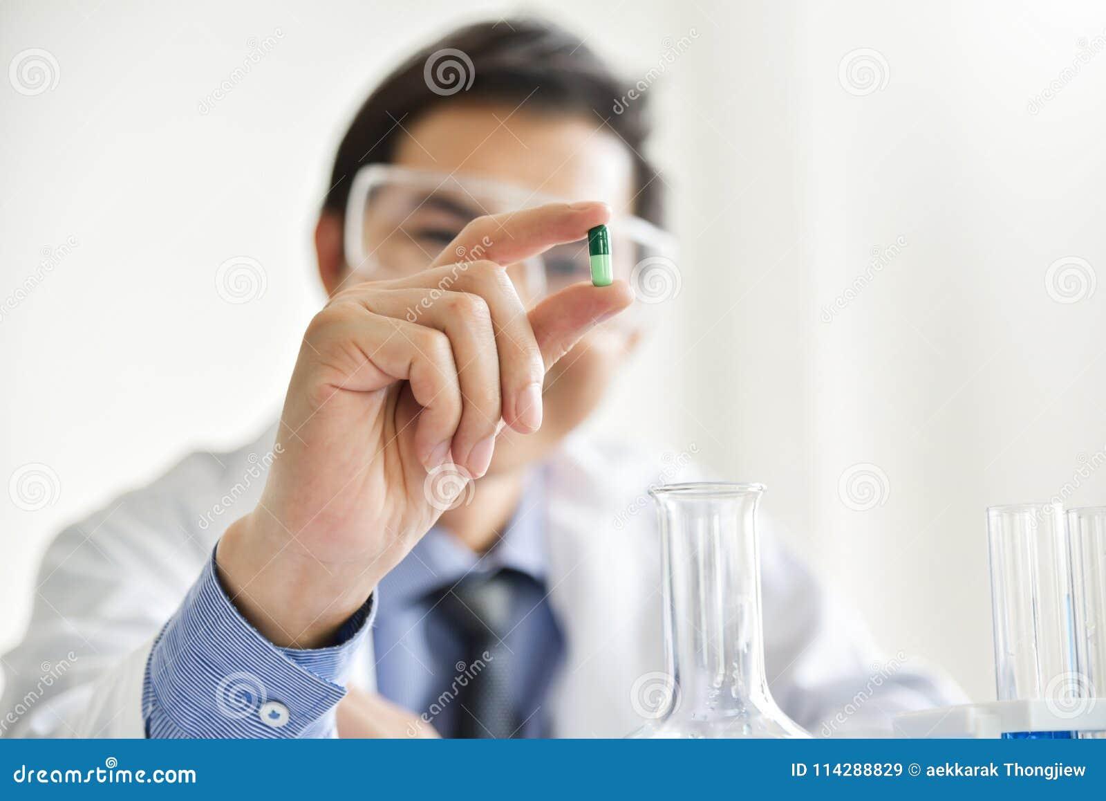 Científico de sexo masculino joven que sostiene una píldora