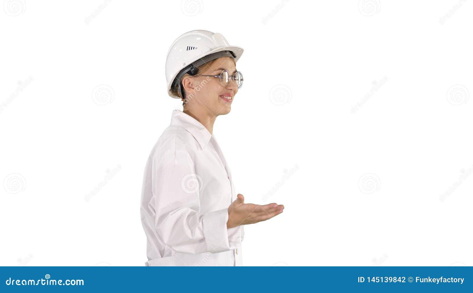Cient?fico joven en capa y el casco de protecci?n del laboratorio que camina y que dice algo en el fondo blanco