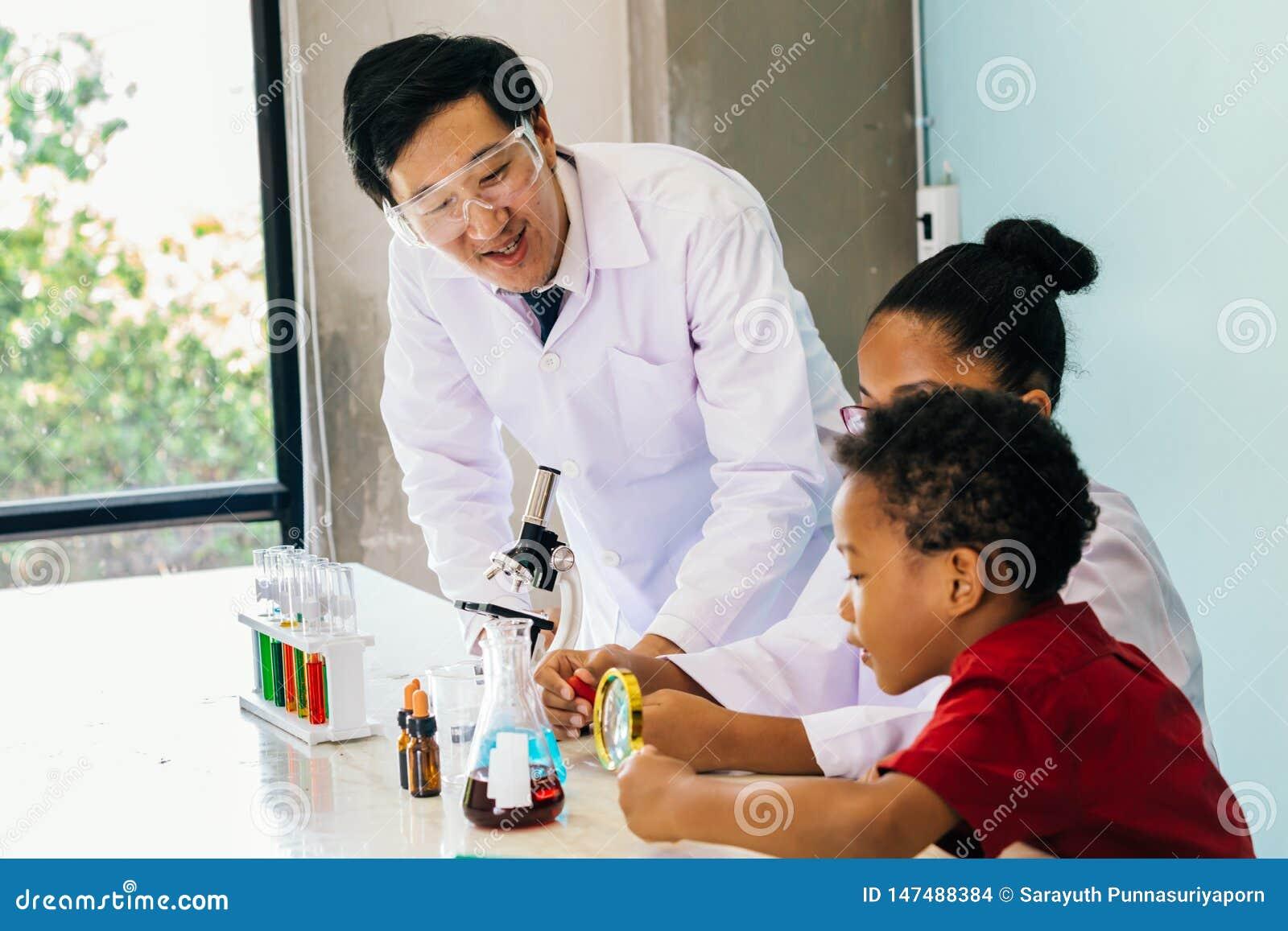 Científico joven que sostiene un frasco y que enseña a dos niños mezclados afroamericanos en el experimento de la química