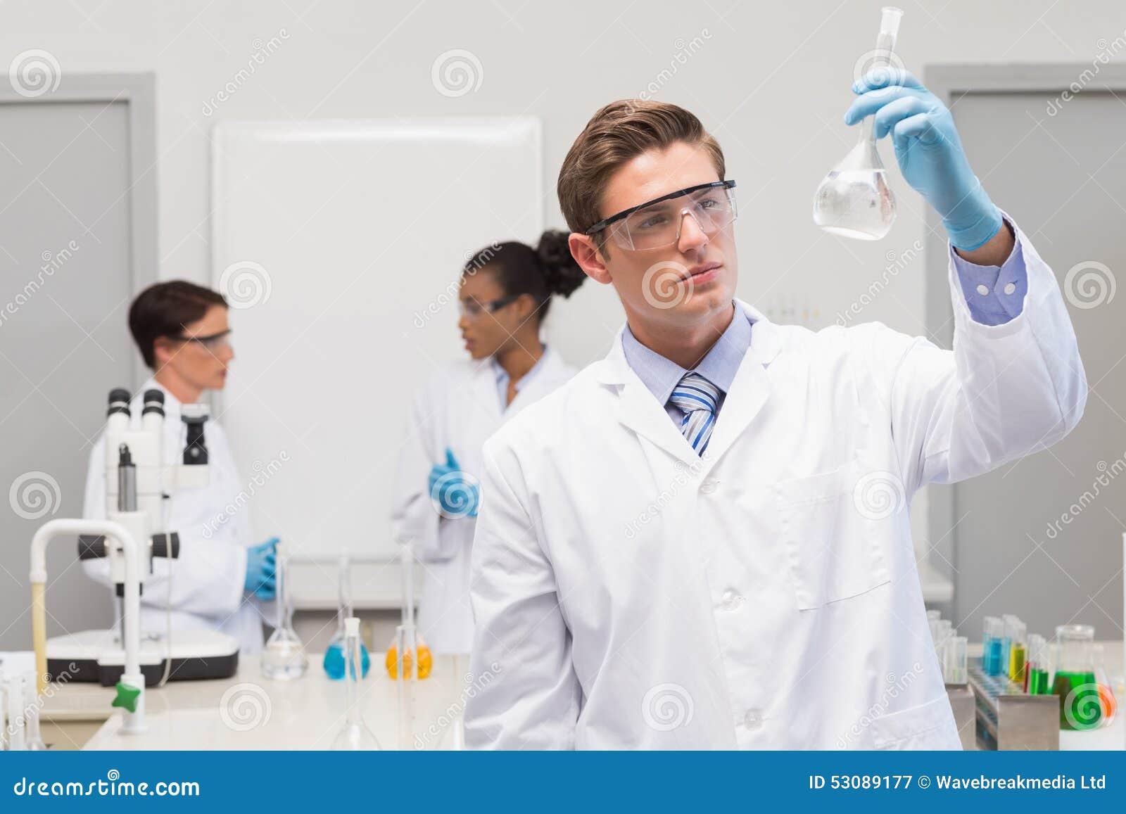 Científico que mira el precipitado blanco mientras que colegas que hablan junto