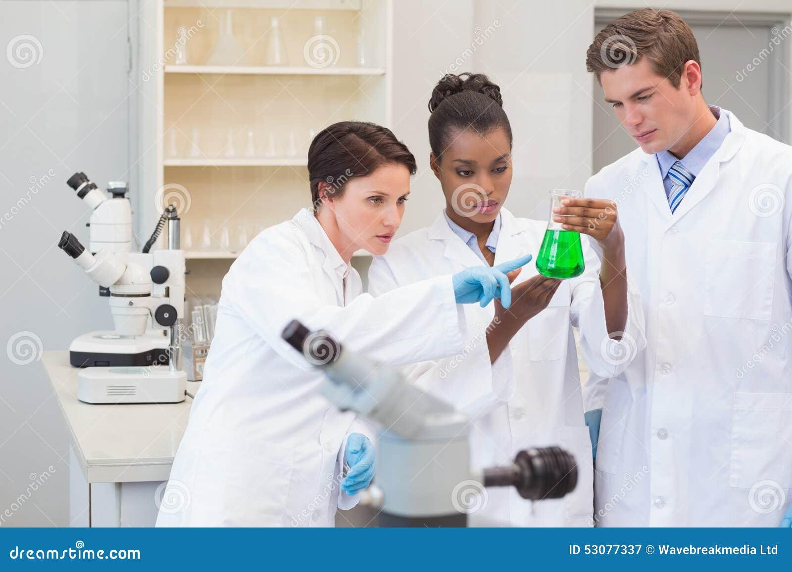 Científicos que miran el precipitado verde