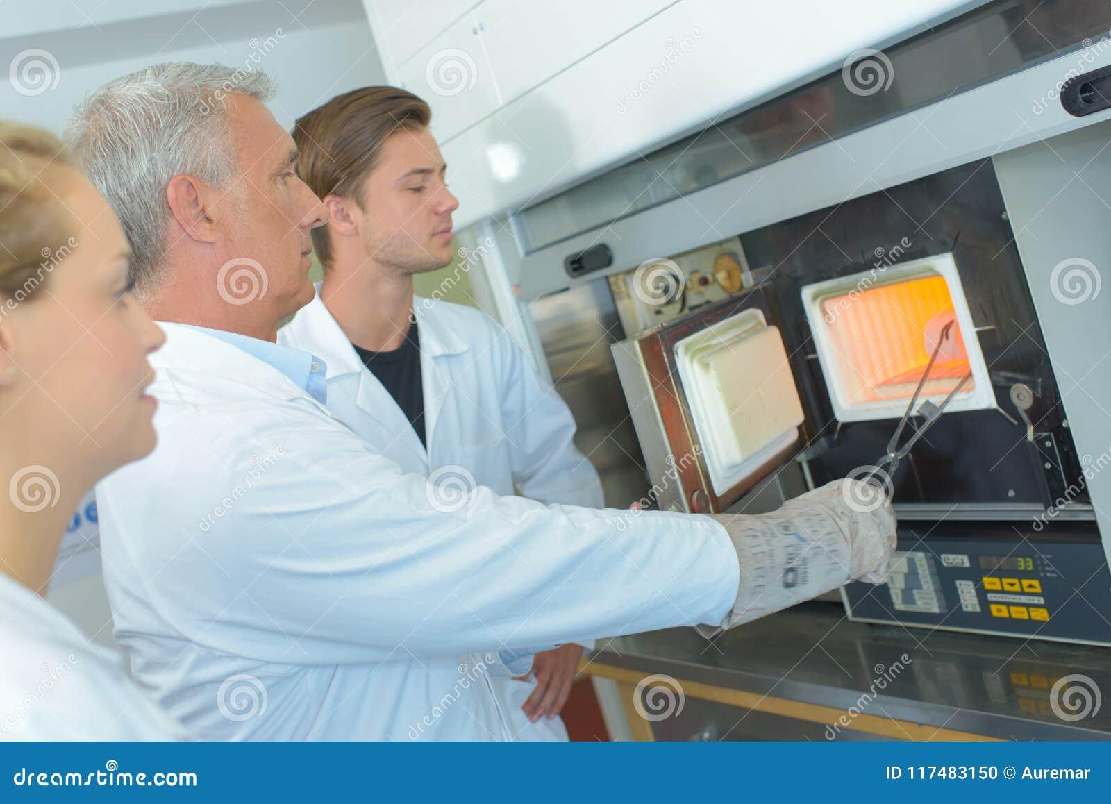 Cientista que remove o objeto do forno com os tenazes de brasa