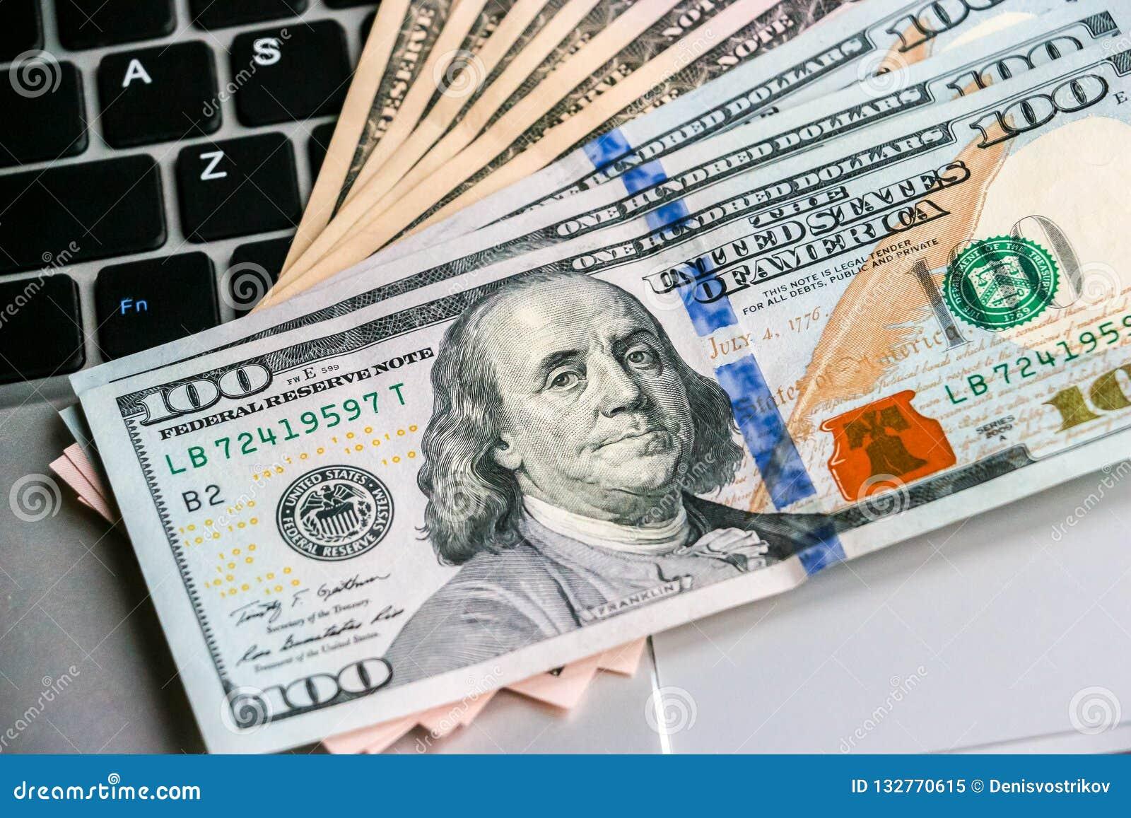 Cientos y cincuenta billetes de banco del dólar que mienten en el teclado del ordenador portátil