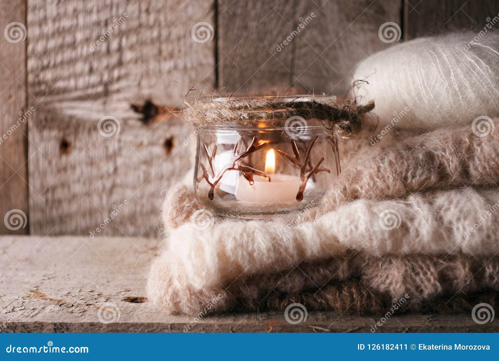Ciepły pulower na drewnianej nieociosanej ławce, świeczka, Spokojna wygodna homely scena Spadek jesieni weekend Monochromatyczny