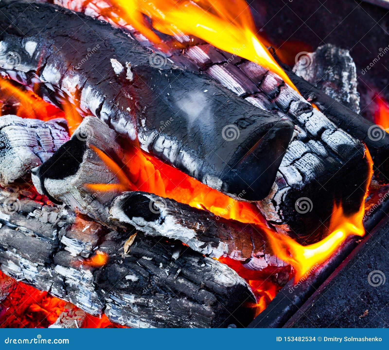 Cierre abierto del fuego para arriba, leña, carbón y ceniza ardientes Fuego en una chimenea abierta