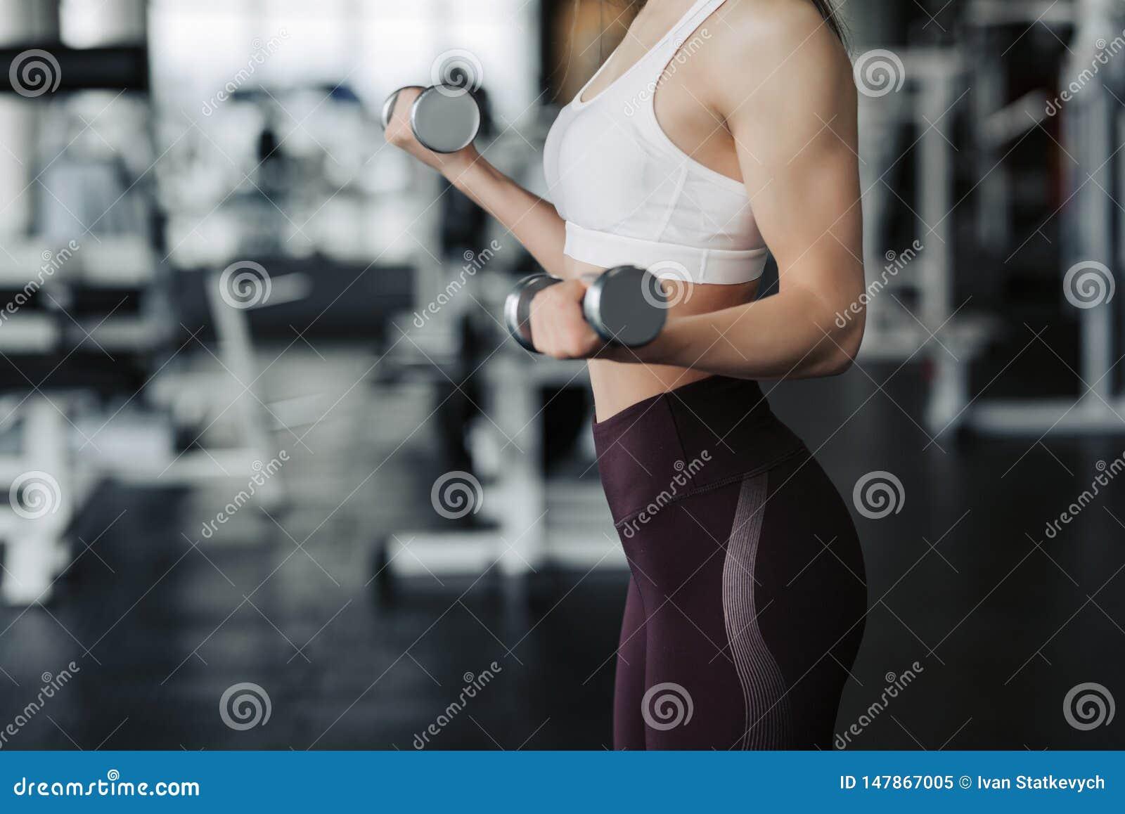 Cierre cosechado del cuerpo para arriba de la mujer atractiva joven en la ropa del deporte que lleva a cabo la pesa de gimnasia d