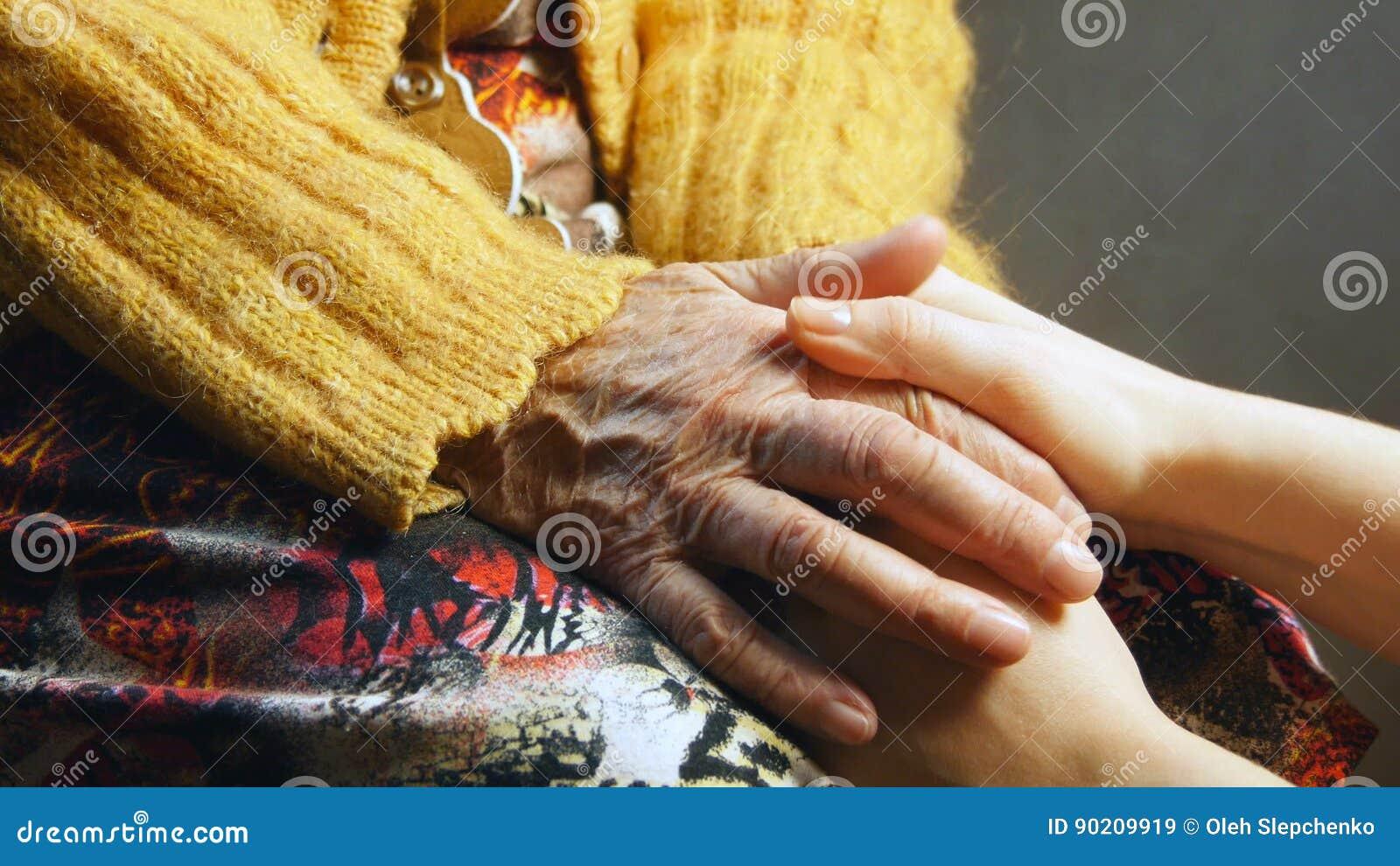 Cierre de la piel de la arruga de la mano del control de la chica joven de la mujer mayor para arriba