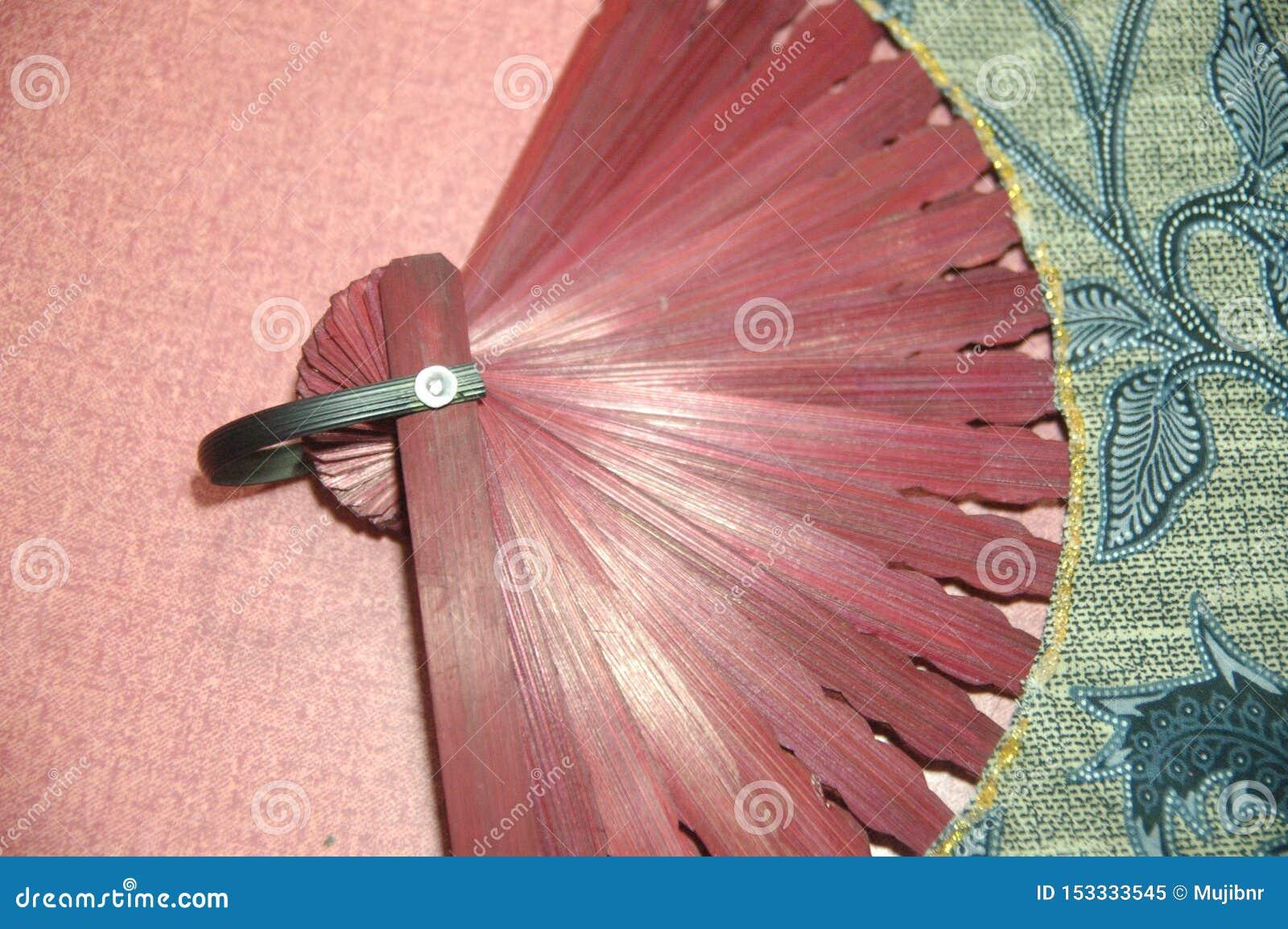 Cierre de madera del color rojo de la fan de la mano de la mujer para arriba
