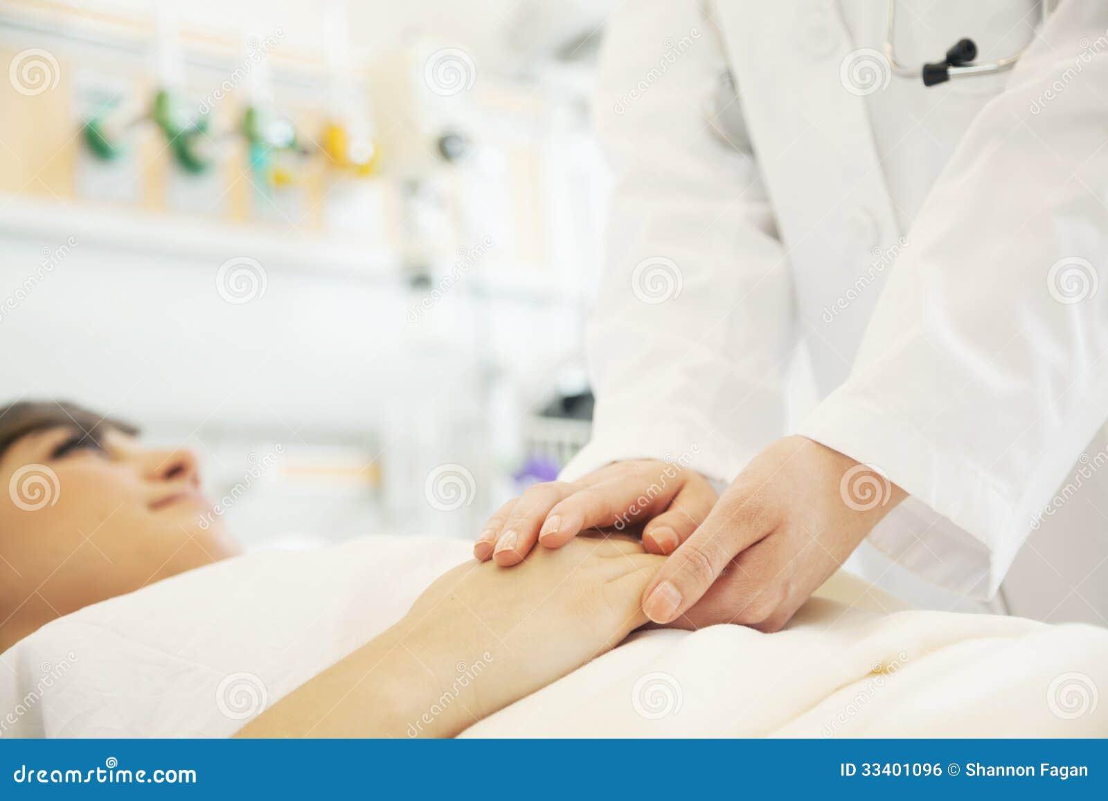 Cierre del doctor levantar las manos de los pacientes que se acuestan en una cama de hospital