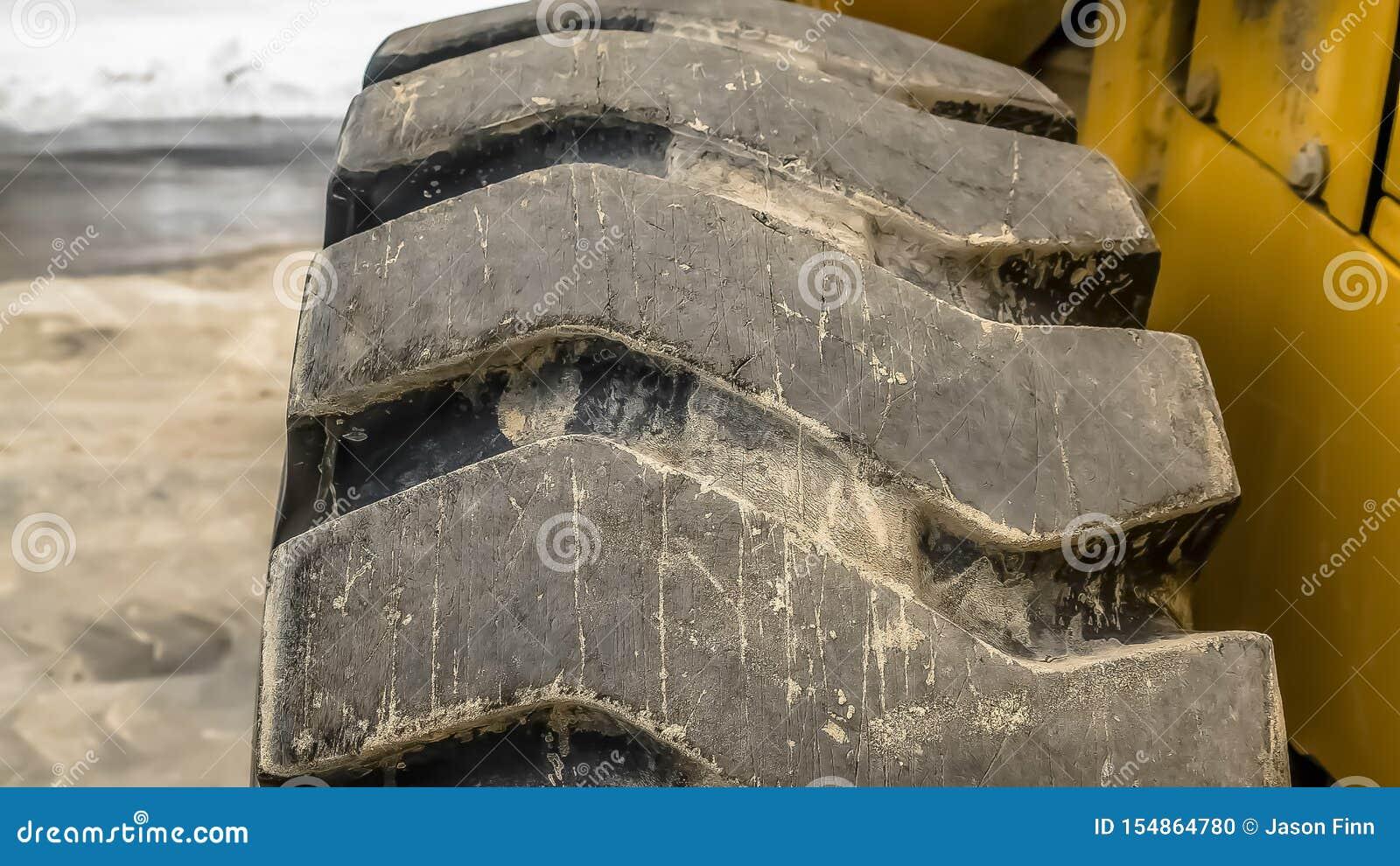 Cierre del marco del panorama para arriba de la rueda de goma negra con la pisada diagonal de un vehículo de la construcción