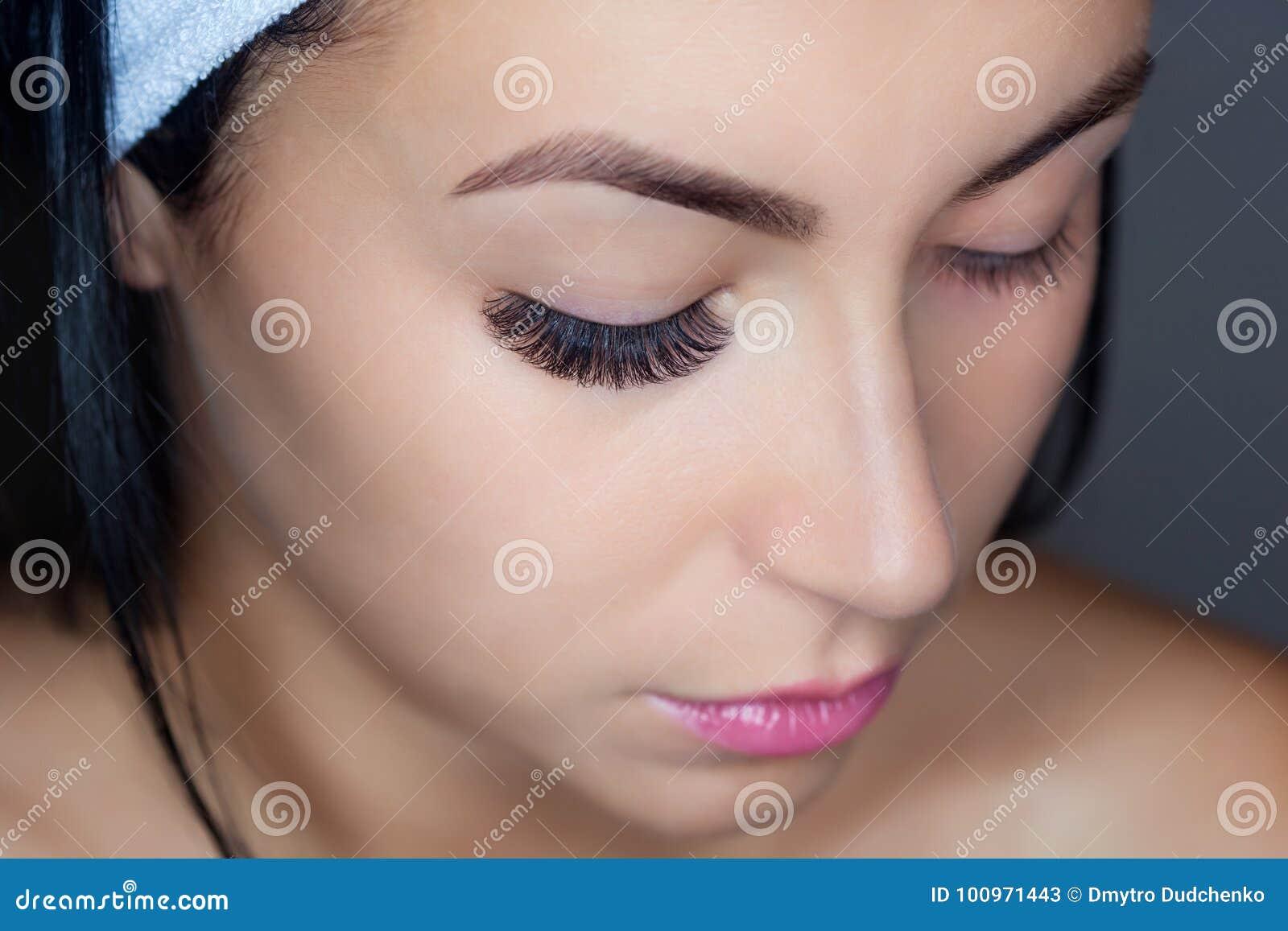 Cierre del procedimiento de retiro de la pestaña para arriba Mujer hermosa con los latigazos largos en un salón de belleza