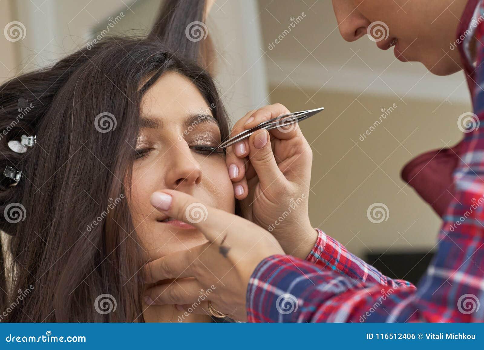 Cierre del procedimiento de retiro de la pestaña para arriba Mujer hermosa con los latigazos largos en un salón de belleza Extens