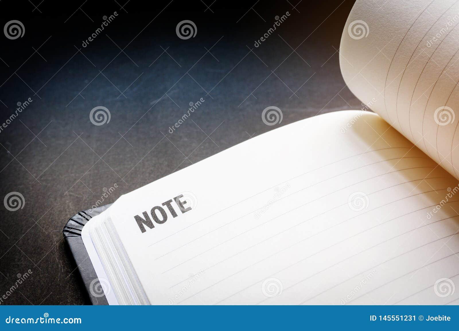 Cierre encima de la l?nea en blanco abierta cuaderno en fondo negro del escritorio en tono de iluminaci?n dram?tico Concepto para