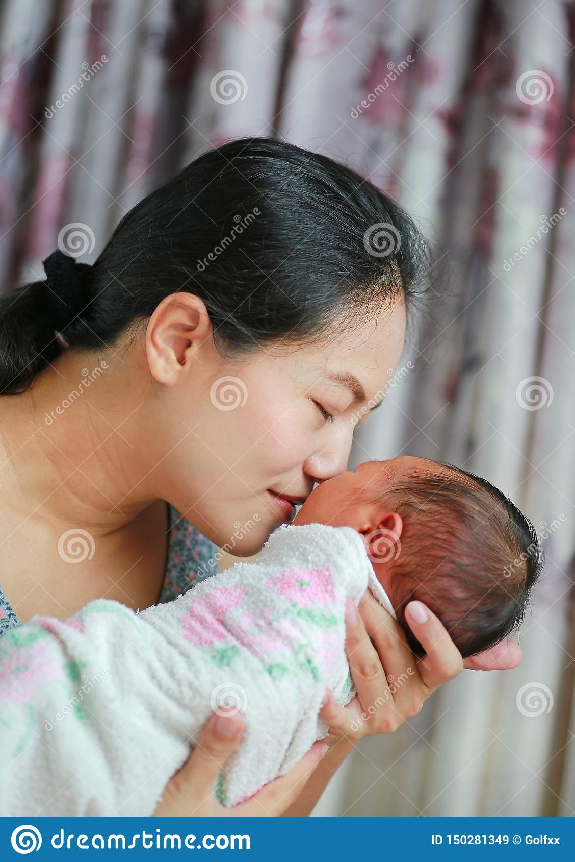 Cierre encima de la madre agradable-que huele al bebé recién nacido
