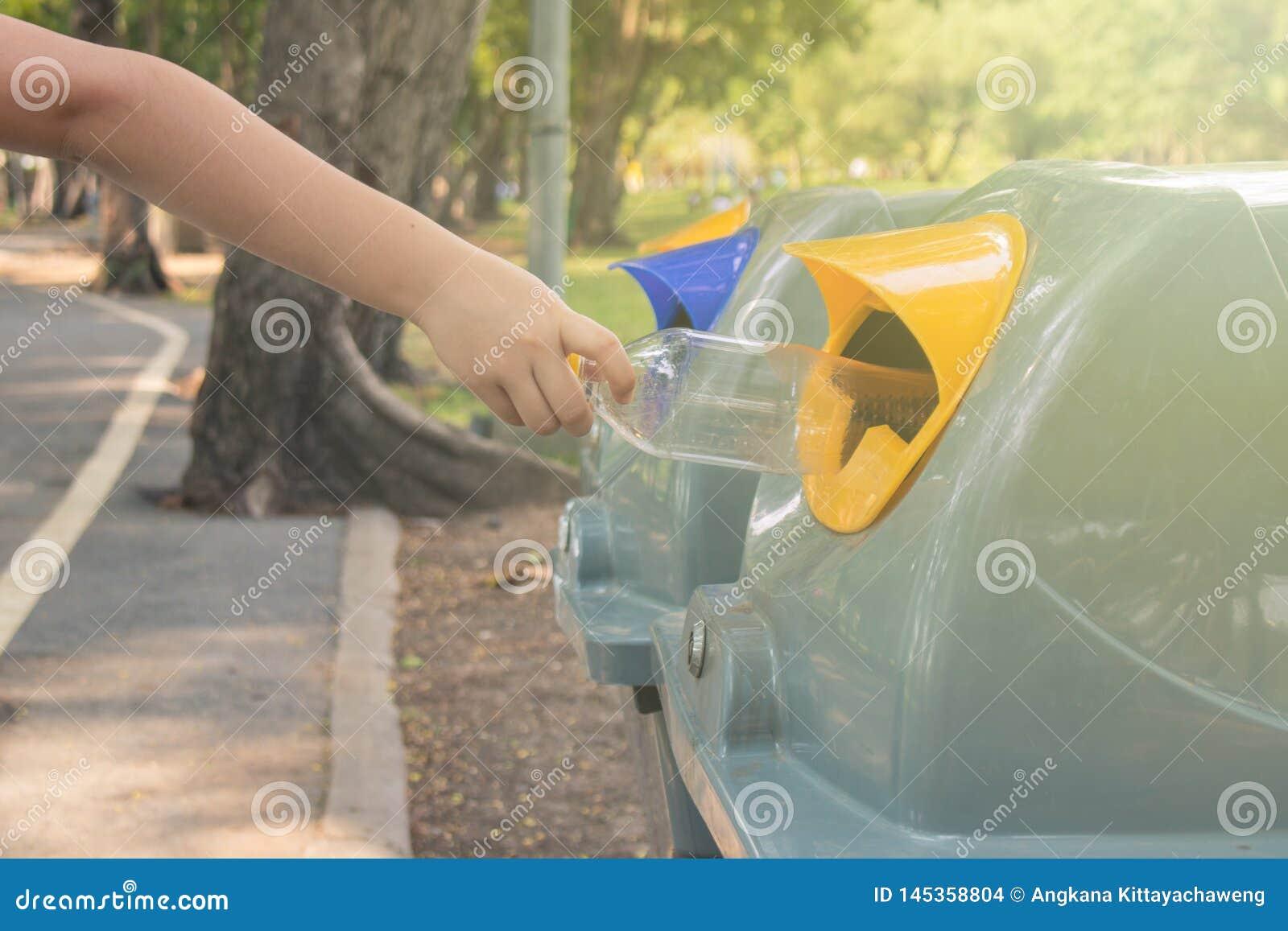 Cierre encima de la mano del peque?o ni?o que pone la botella pl?stica usada en papeleras de reciclaje p?blicas o cubos de la bas