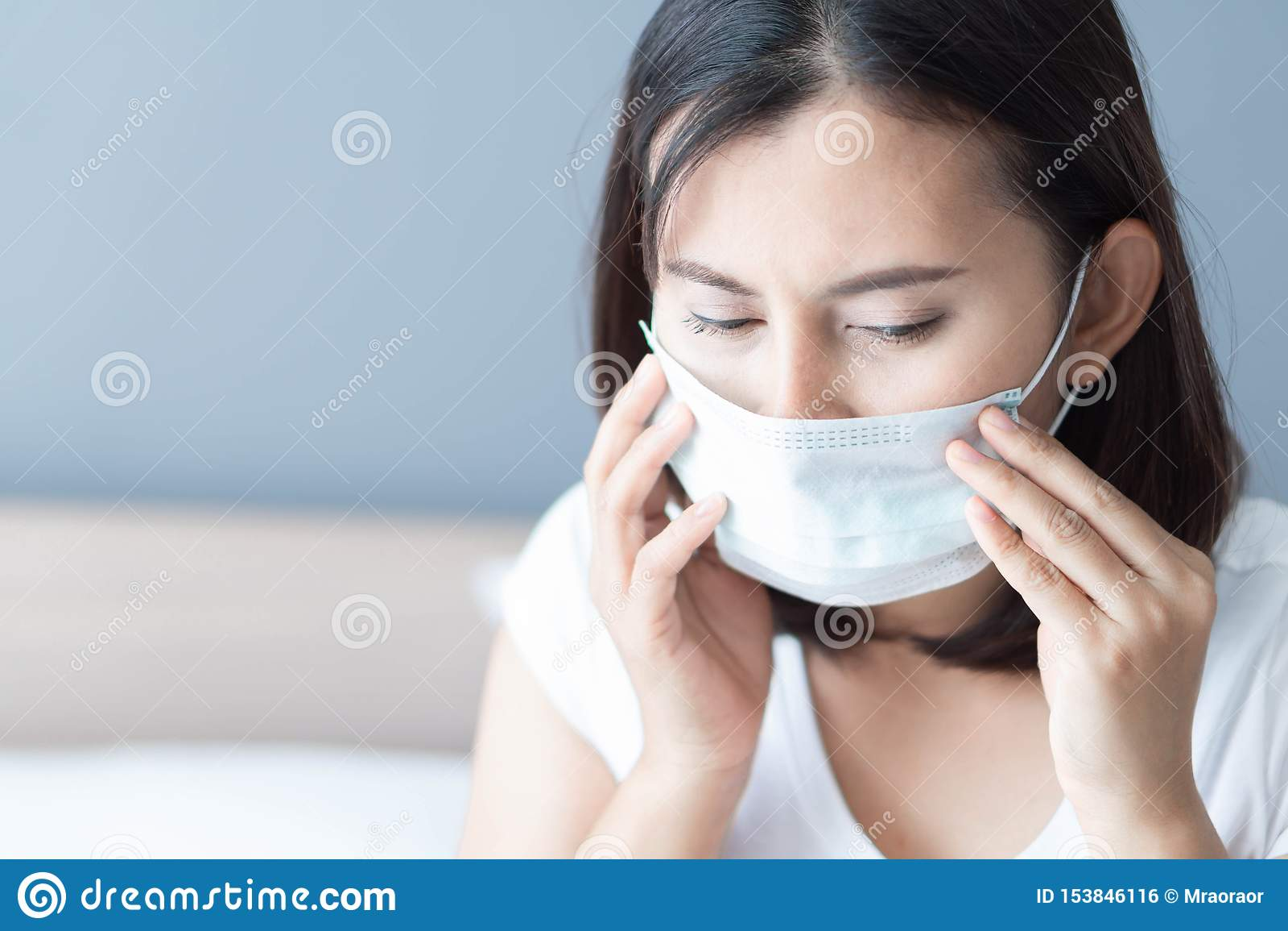 Cierre encima de la mujer enferma que lleva la cara médica de la máscara que miente en la cama blanca, la atención sanitaria y el