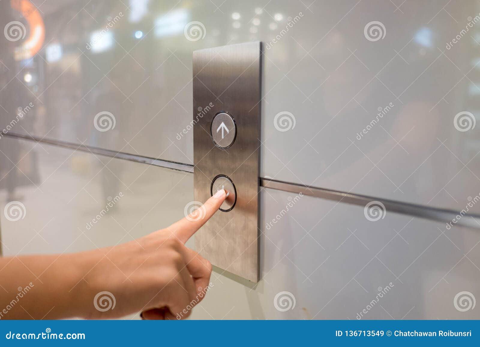 Cierre encima de la prensa de la mano del waman un botón ascendente del elevador dentro del edificio para el piso de alto nivel s