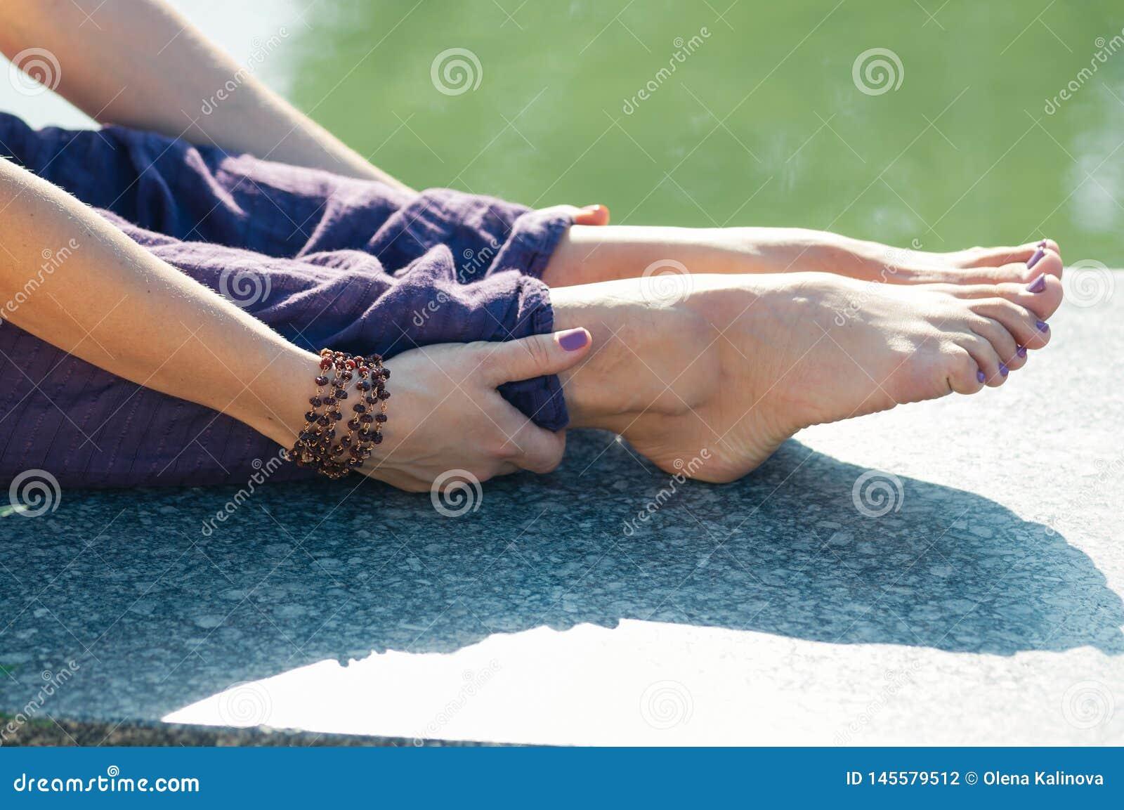 Cierre encima de las manos femeninas que llevan a cabo actitud que se sienta del pie