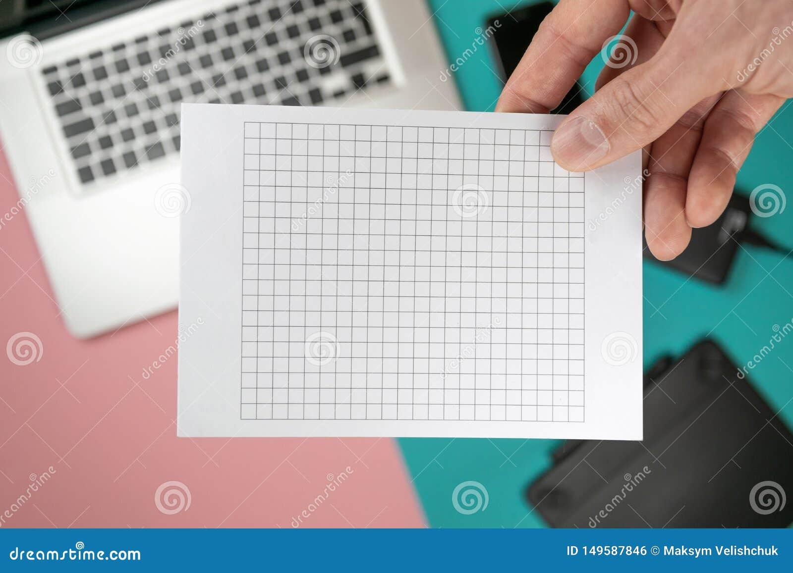 Cierre encima de las manos masculinas que llevan a cabo el espacio en blanco de papel para el papel del dise?o