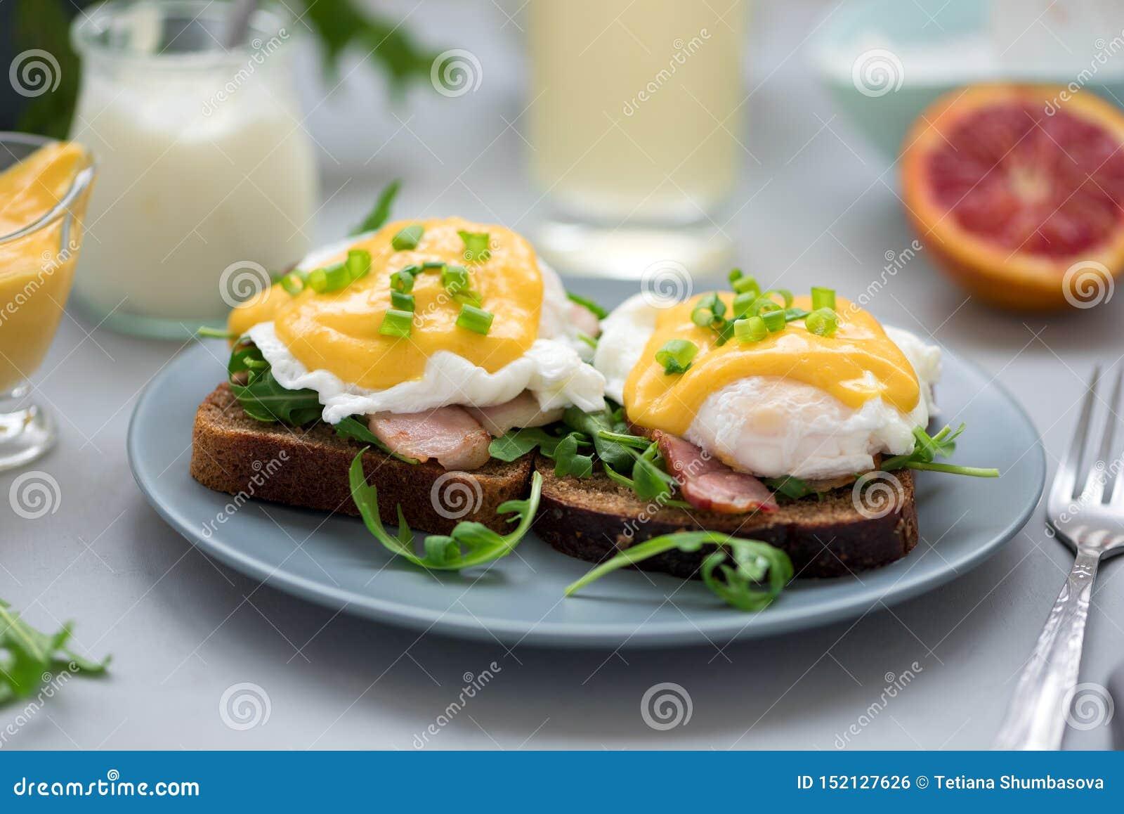 Cierre encima de los huevos Benedicto con arugula, salsa del tocino y del hollandaise en fondo de madera gris Foco suave Concepto