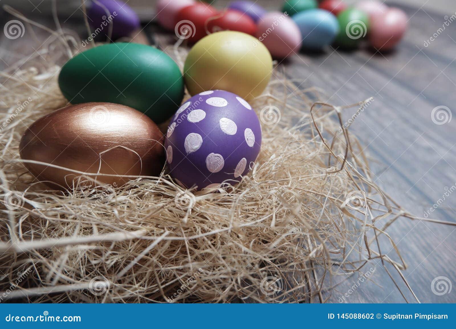 Cierre encima de los huevos de Pascua coloridos en jerarquía en la tabla de madera