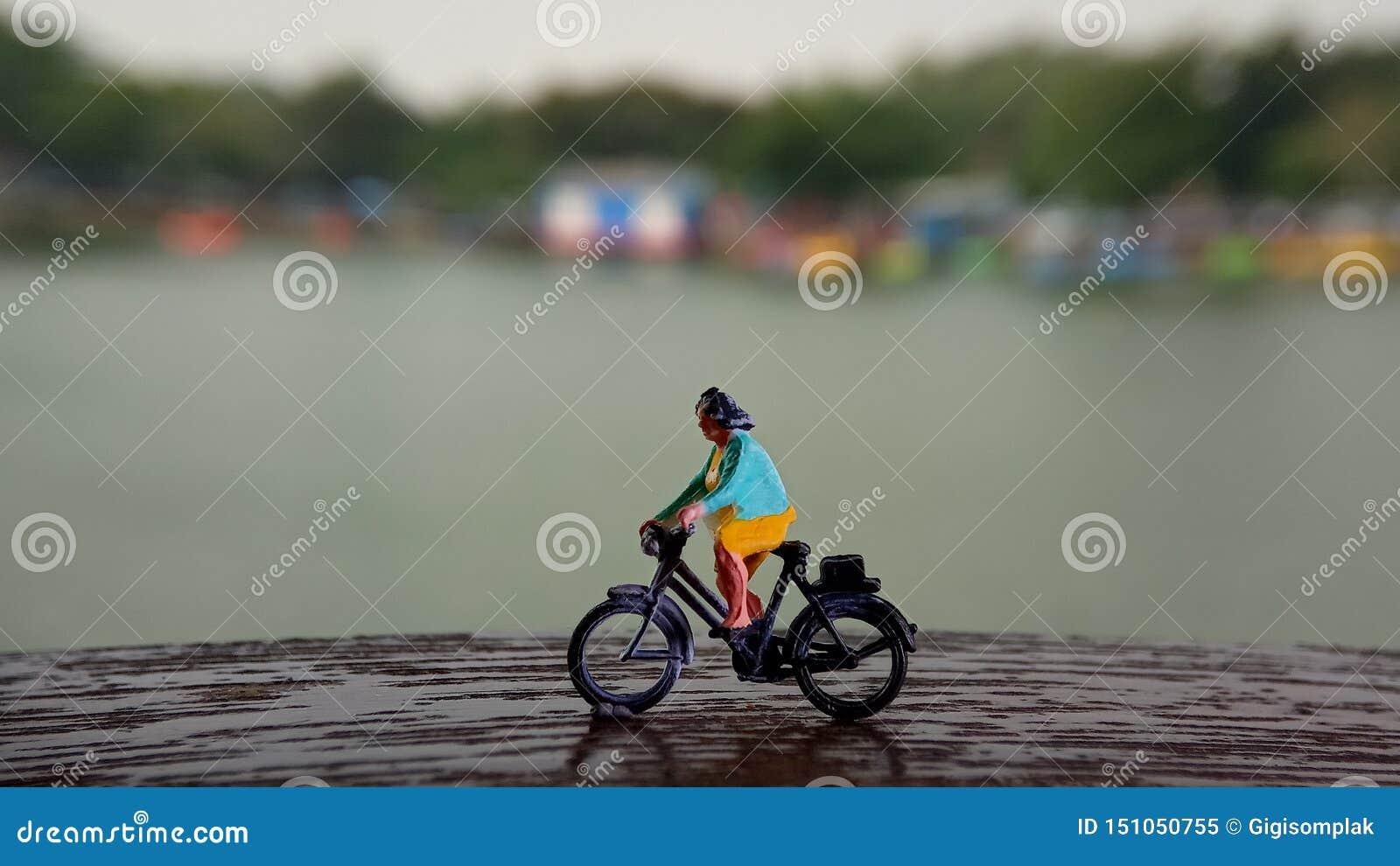 Cierre encima de los juguetes de Mini Figure Woman que montan en bicicleta en la manera de la trayectoria del lado del río con el