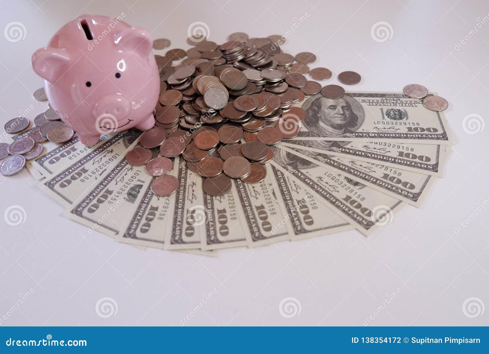 Cierre encima de Piggybank con las monedas y el dinero sobre el escritorio