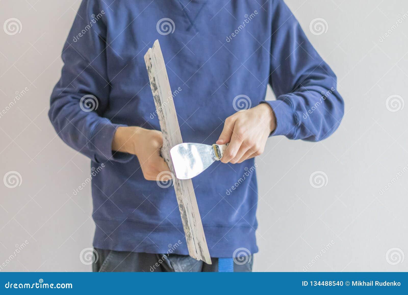 Cierre encima del hombre que sostiene los cuchillos de masilla que enyesan el hogar f de la pared, del funcionamiento y de la rep