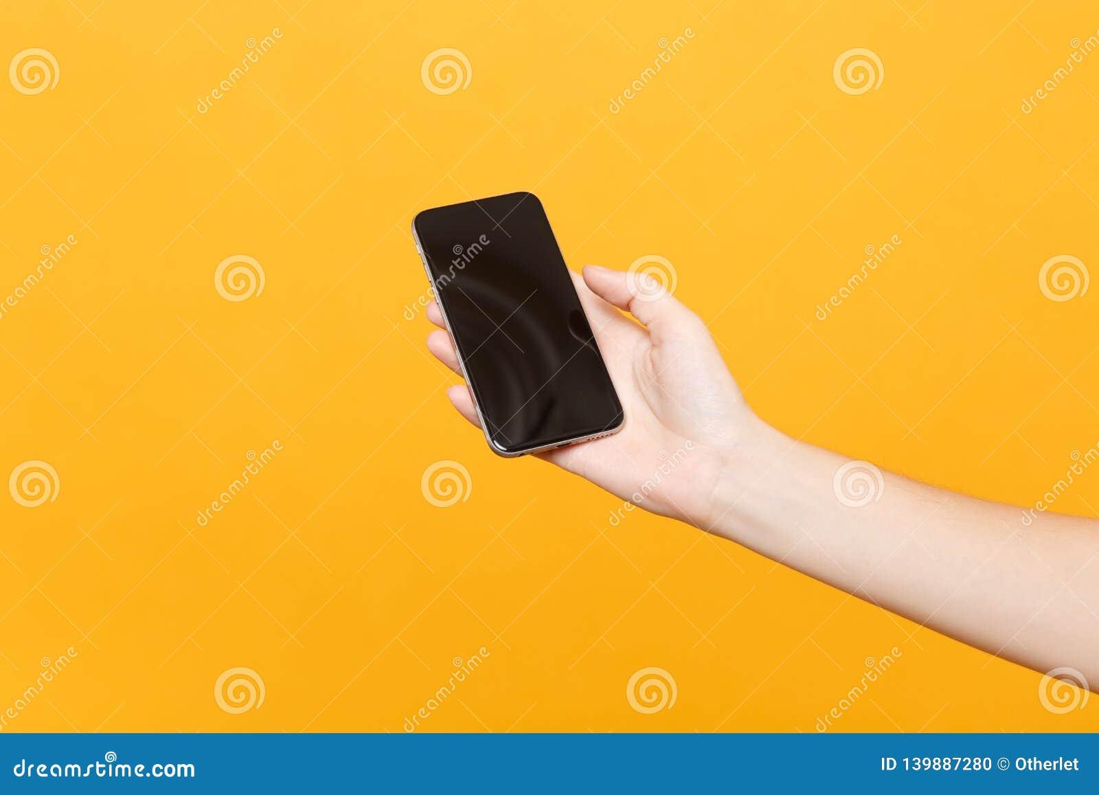 Cierre encima del teléfono móvil femenino del control a disposición con la pantalla vacía en blanco con el lugar para el texto o