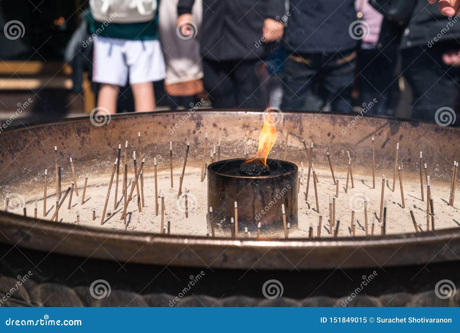 Cierre hasta incienso en la hornilla de incienso que palillos ligeros turísticos del incienso para rogar en el templo de Todai-ji