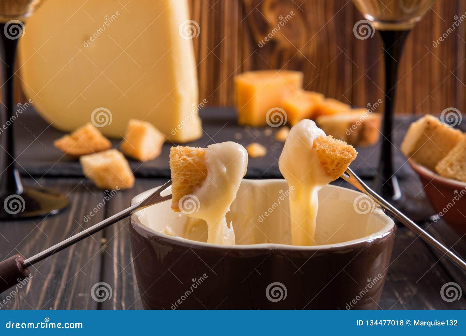 Cierre para arriba Cena suiza gastrónoma de la  fondue  en una tarde del invierno con quesos clasificados en un tablero junto a u