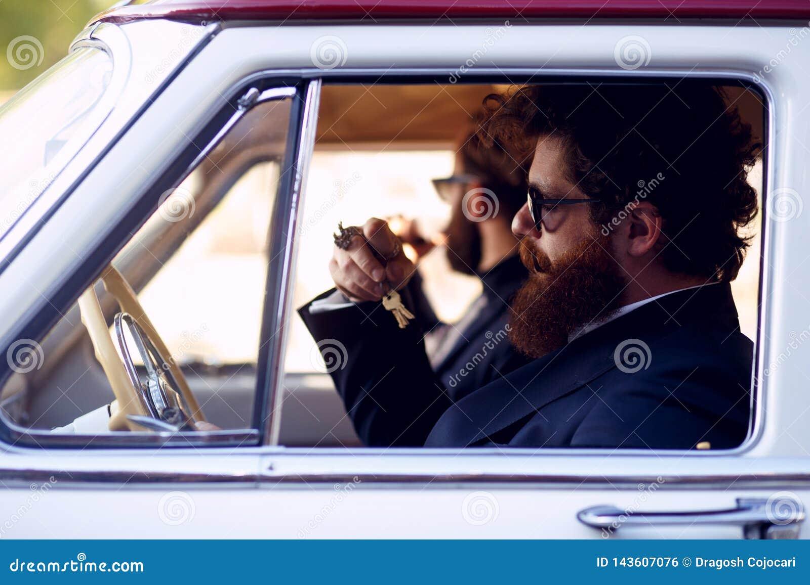 Cierre para arriba de a dos hombres barbudos, en las gafas de sol y los trajes elegantes negros, fumando los cigarrillos dentro d