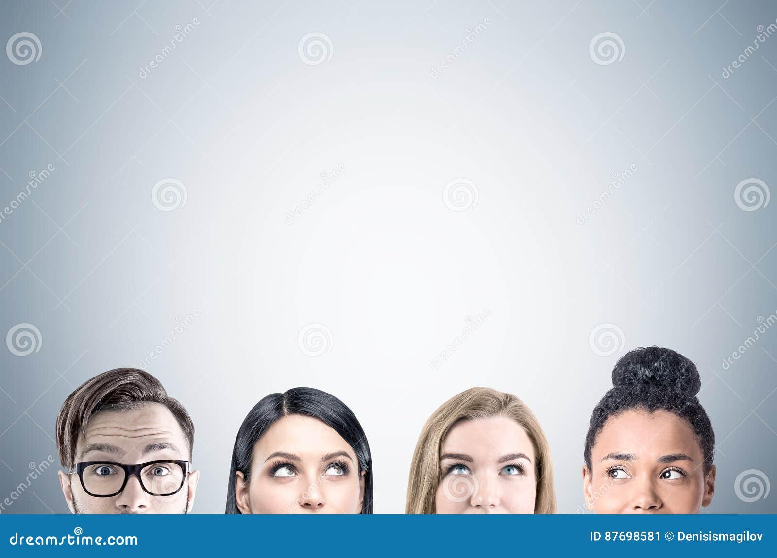 Cierre para arriba de las caras del equipo del negocio, gris