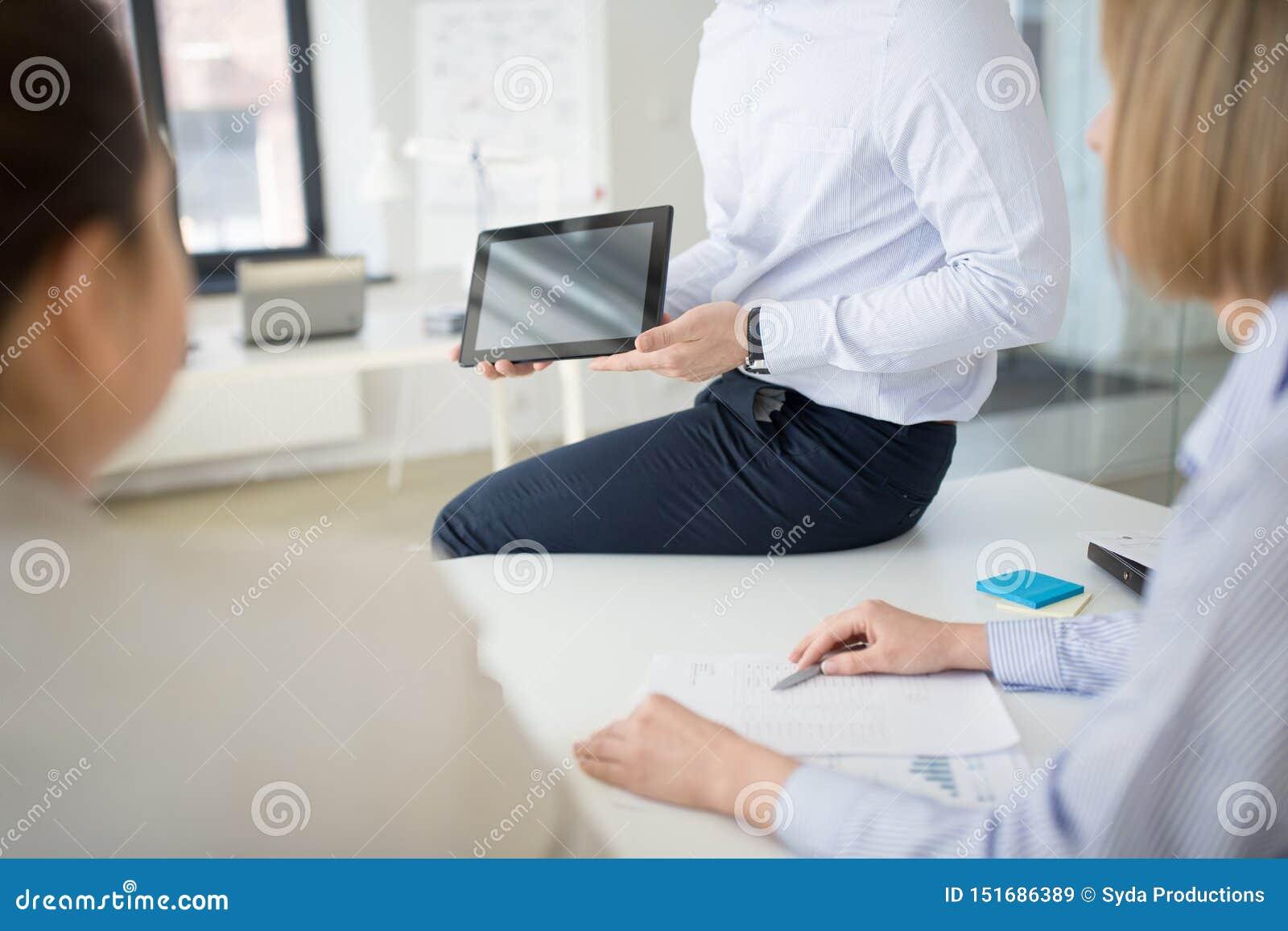 Cierre para arriba del equipo del negocio con PC de la tableta en la oficina